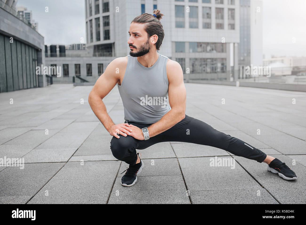 Immagine Del Giovane Uomo Stratching La Gamba E Il Riscaldamento Egli Fa Piccoli Esercizi Per Le