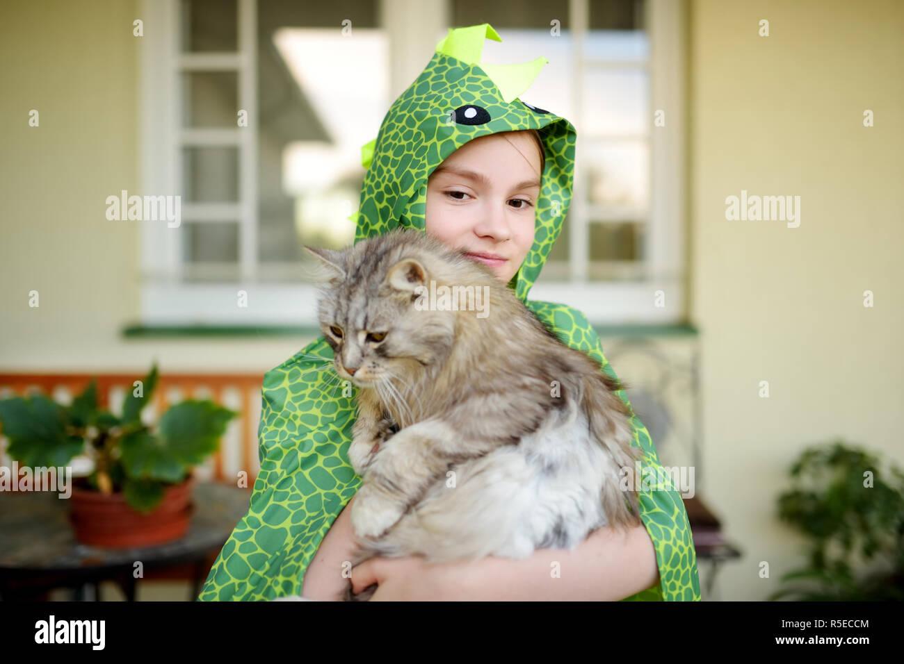 Ragazza carina indossando il costume di fantasia mentre tiene il suo gatto  sulla soleggiata giornata estiva 1eaef19b048