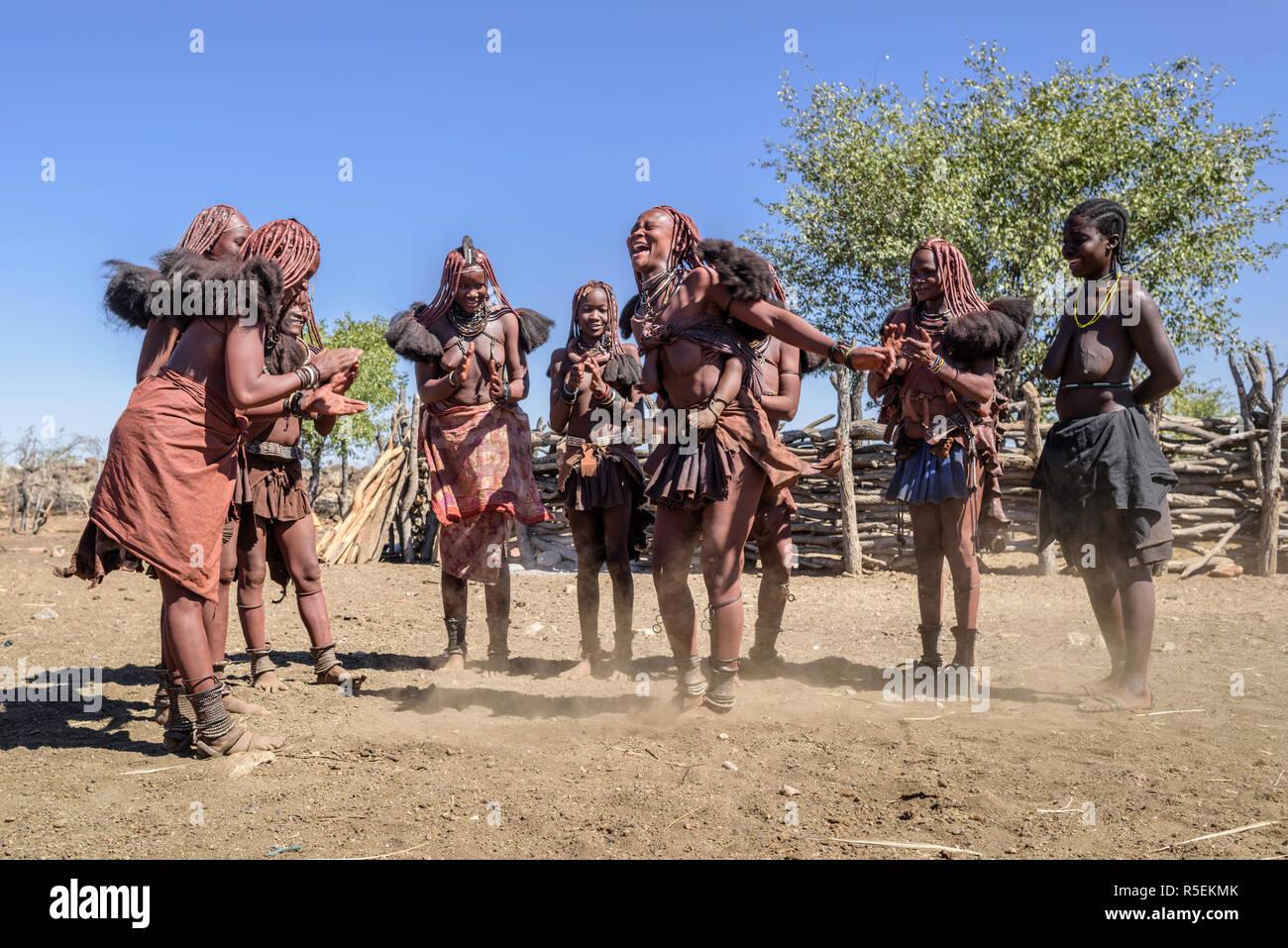 Un gruppo di donne himba con abiti tradizionali balli in un cerchio, alcuni di loro mentre trasportano i loro bimbi sulle loro spalle. Foto Stock