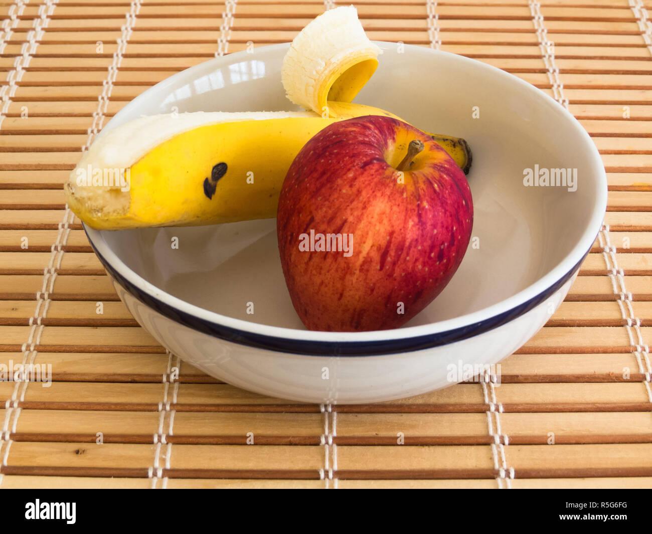 Apple e banana recipiente interno su strisce di legno tabella Immagini Stock