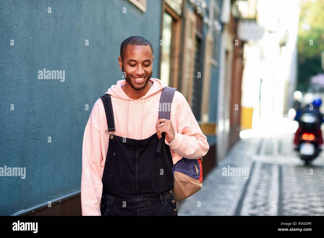 Giovane uomo nero indossando abiti casual sorridendo a piedi giù per la strada. Millenaria ragazzo africano con bib pants all'aperto Foto Stock