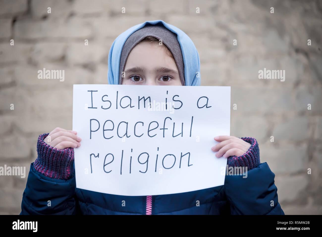 """Refugee ragazza con una scritta su un foglio bianco """"l'Islam è una religione pacifica' Immagini Stock"""