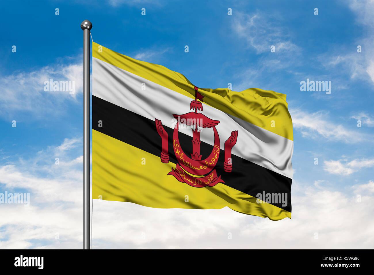 Bandiera del Brunei sventolare nel vento contro bianco torbido cielo blu. Bruneian bandiera. Immagini Stock