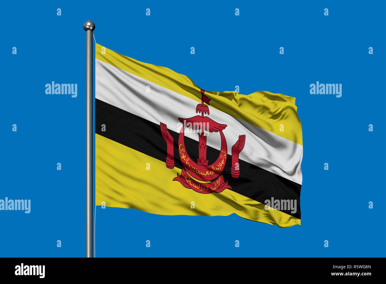 Bandiera del Brunei sventolare nel vento contro il profondo blu del cielo. Bruneian bandiera. Immagini Stock