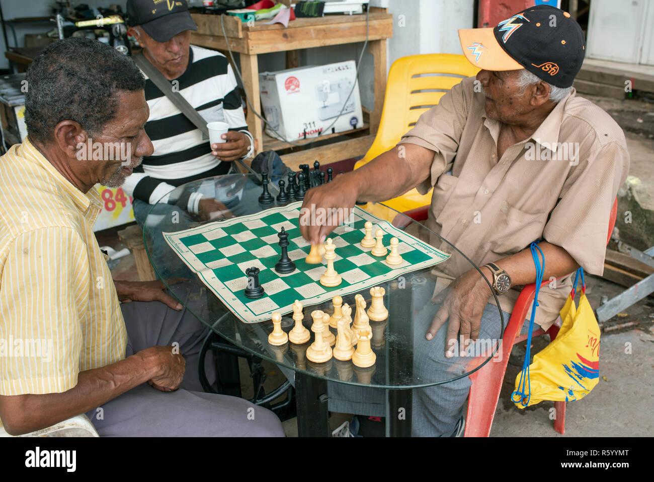 Afro-Colombian uomini giocare a scacchi al di fuori di una macchina da cucire repair shop. Lo stile di vita quotidiano in Cartagena de Indias, Colombia. Ott 2018 Immagini Stock