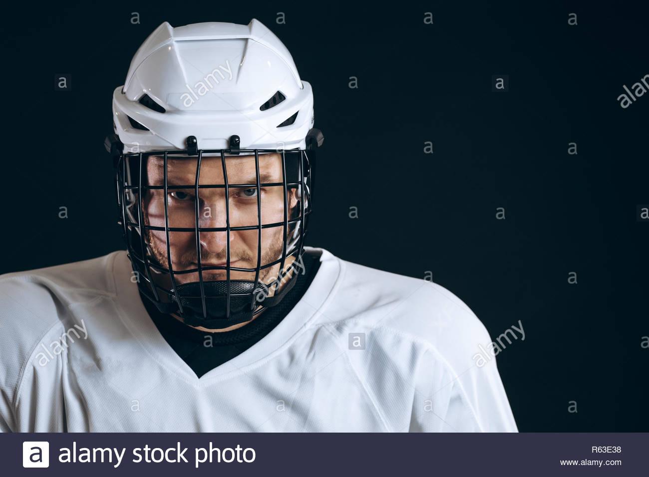 02804517cf573 ... ritratto di fiducioso brave giocatore di hockey in bianco uniforme con  casco protettivo guardando la telecamera