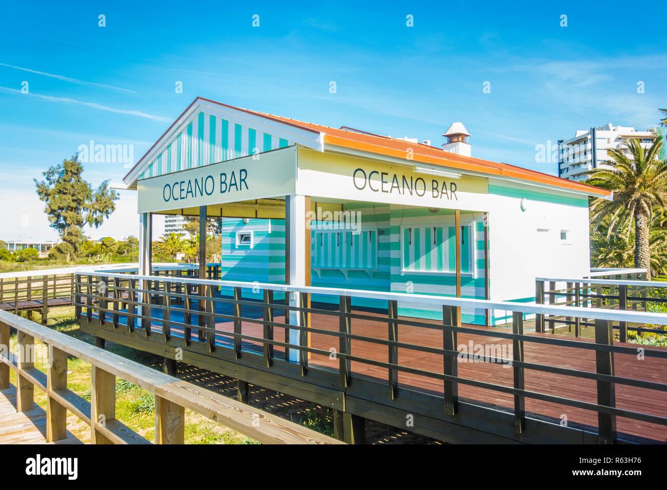Il turchese a strisce bianche e il beach bar 'oceano bar' e passerella che conduce alla spiaggia Immagini Stock