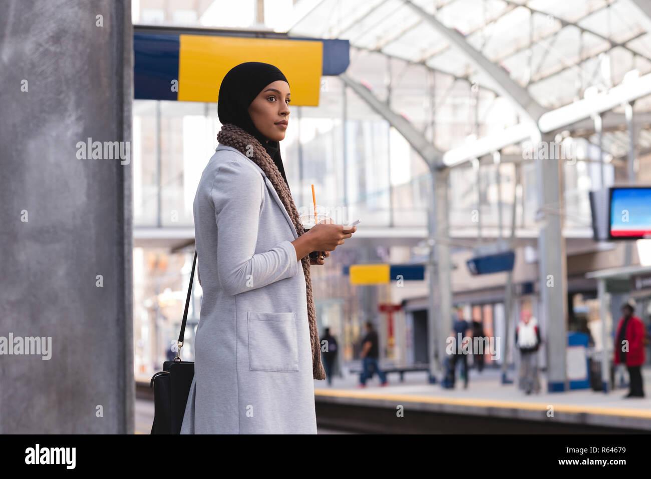 La donna in attesa del treno mentre si utilizza il telefono cellulare alla stazione ferroviaria Foto Stock
