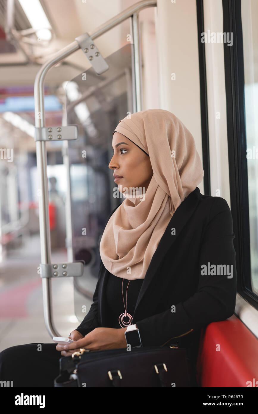 Donna che utilizza il telefono cellulare mentre si è in viaggio in treno Foto Stock