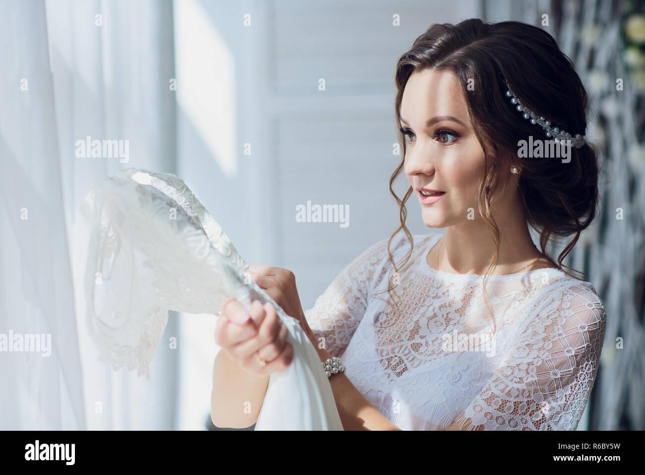 70cf216b6175 Bella bruna sposa in seta vestaglia e lacy velo holding abito da sposa su un  appendiabiti