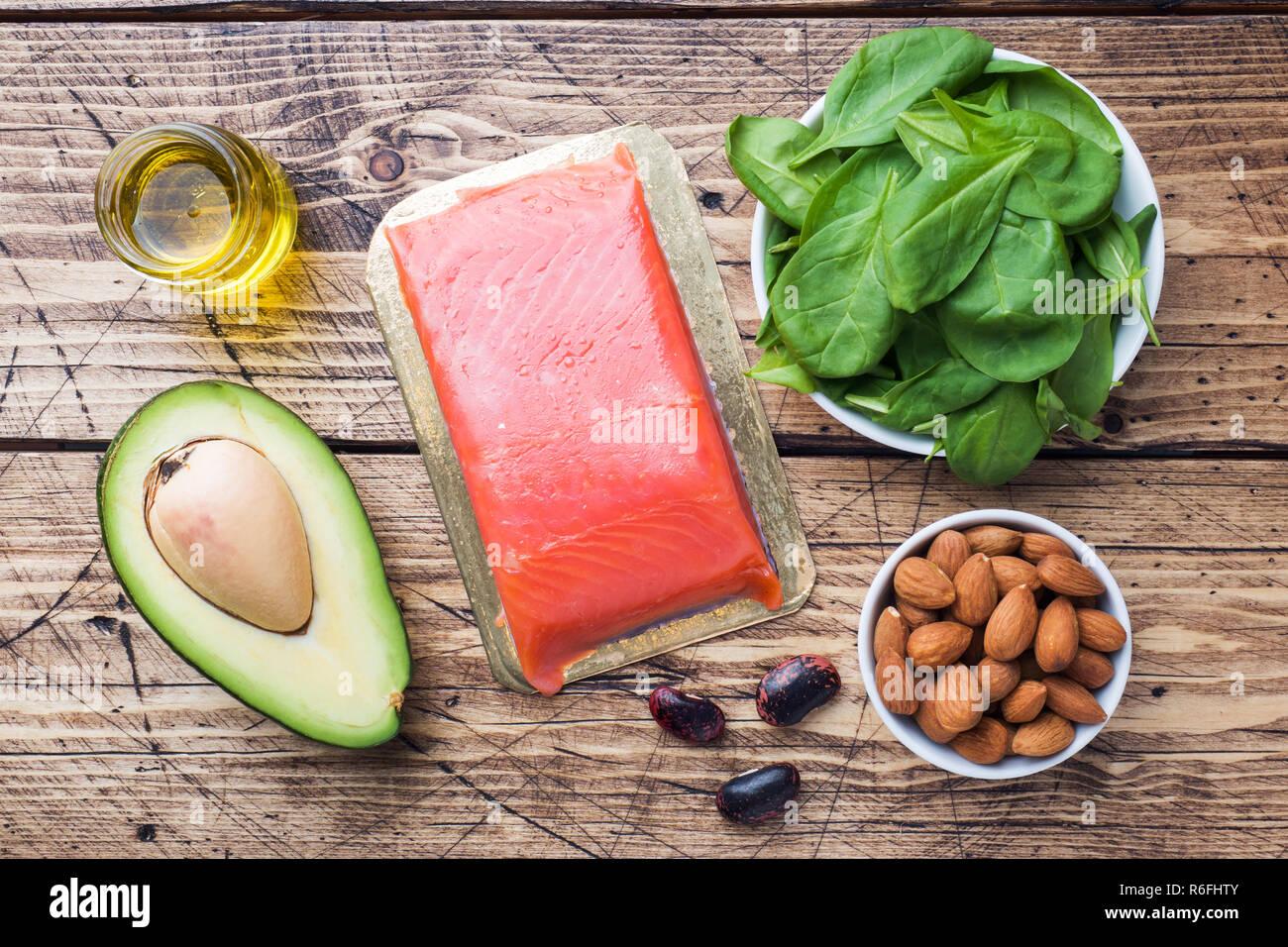 Concetto di alimenti sani prodotti antiossidanti: pesce e avocado, dadi e olio di pesce, pompelmo su sfondo di legno Immagini Stock