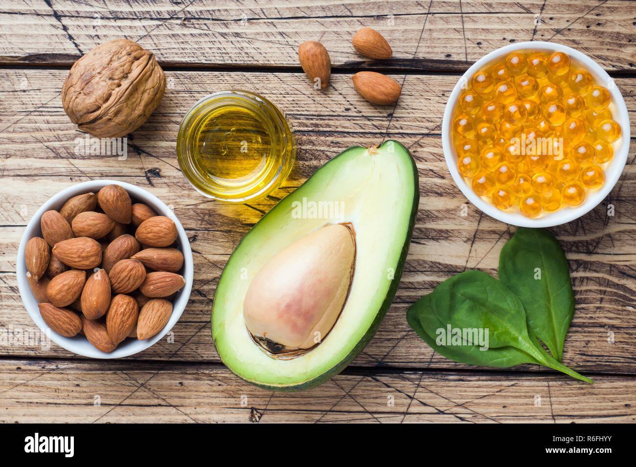 Concetto di alimenti sani prodotti antiossidante di avocado, dadi e olio di pesce, pompelmo su sfondo di legno Immagini Stock