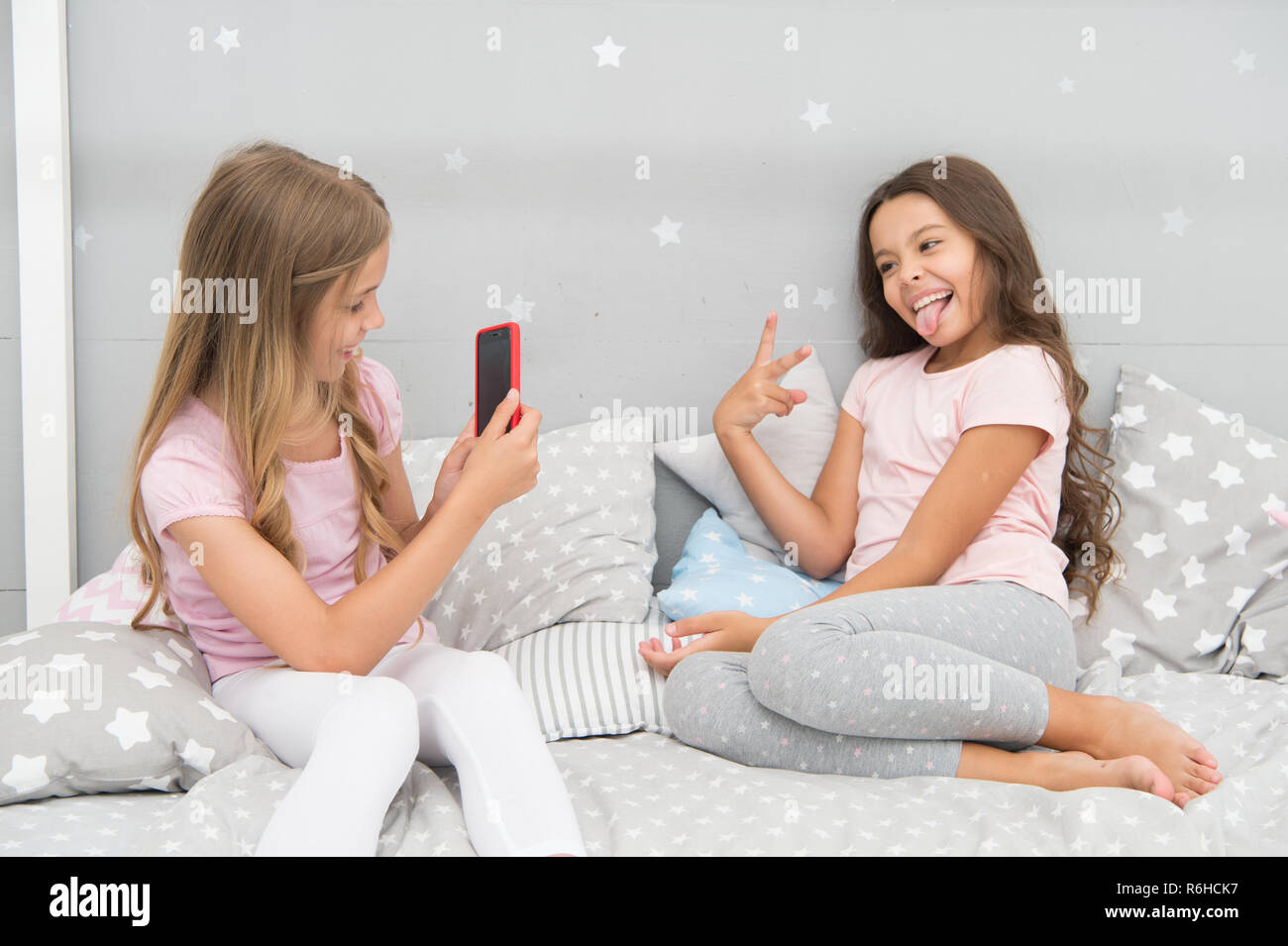 Reti sociali di concetto. Ragazze amici prendendo la foto per le reti sociali. Streaming Online vlog channel. Sorelle in pigiama camera da letto potrete rilassarvi e prendere foto divertenti per il social network account. Svago e divertimento. Immagini Stock