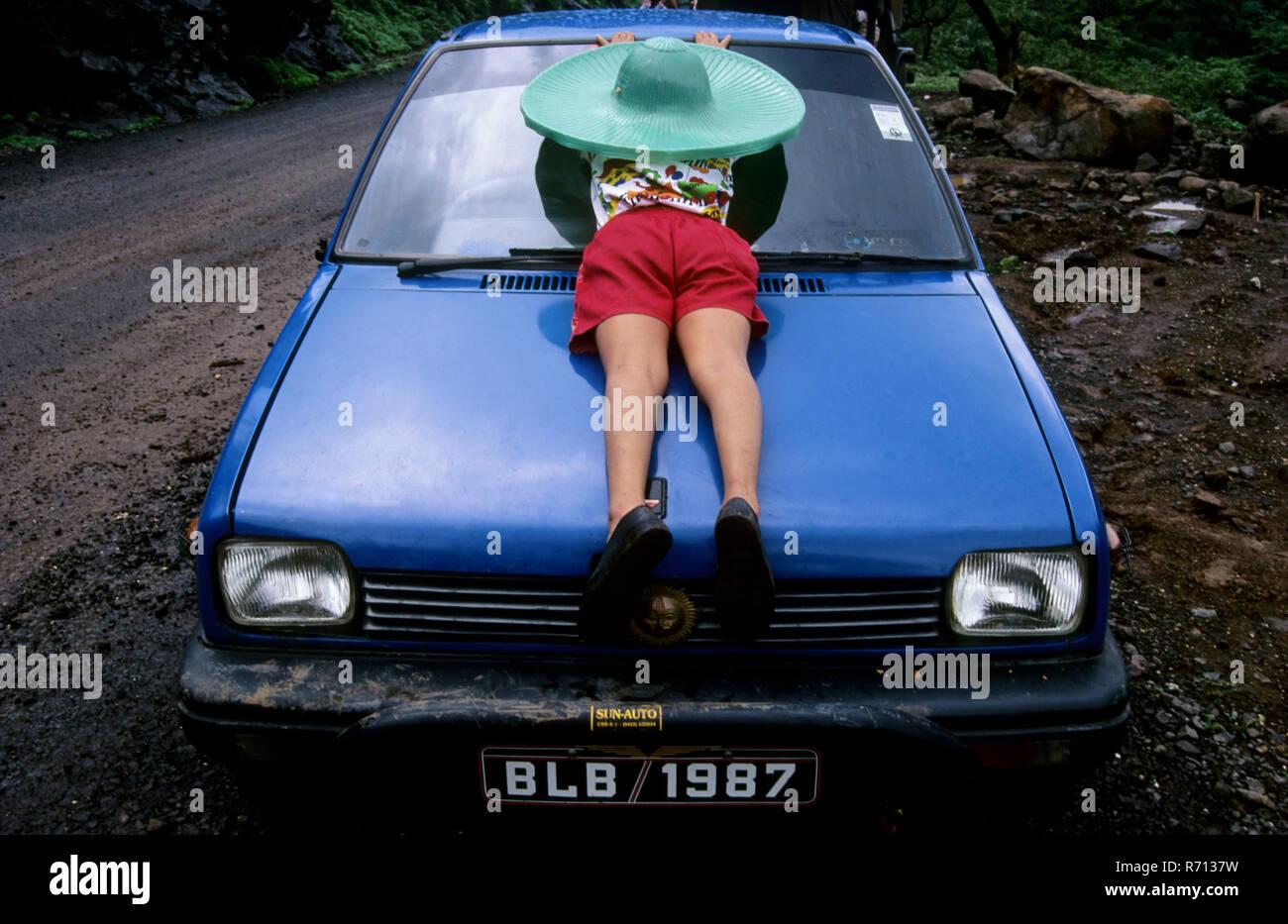 Un angolo di rara vista del ragazzo dormiva sul cofano di maruti car Immagini Stock
