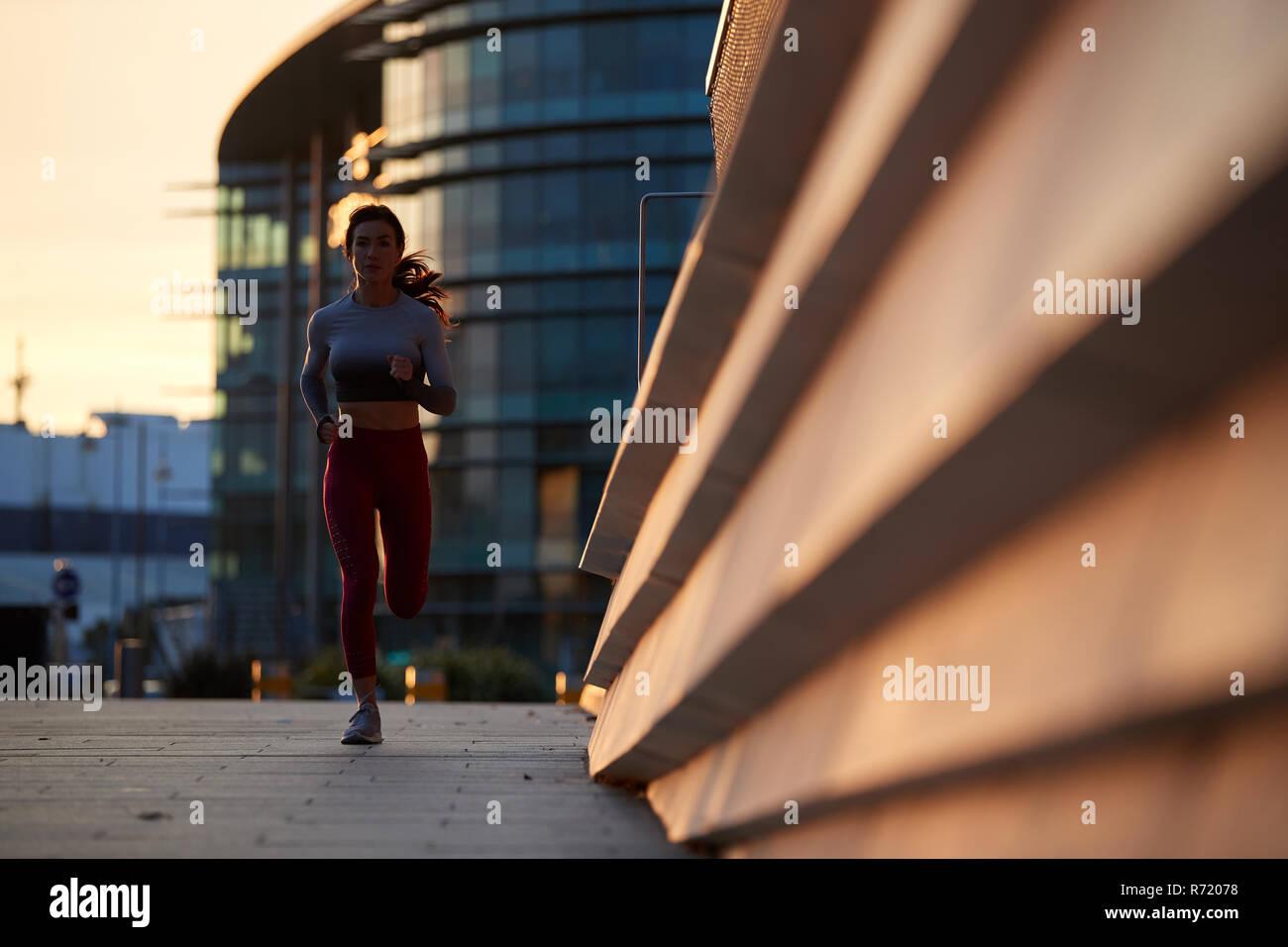Single Caucasian Female jogging in un centro della città al tramonto Foto Stock