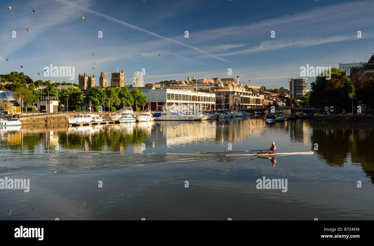 Bristol, Inghilterra, Regno Unito - 11 agosto 2018: un vogatore treni in Bristol flottante della banchine del porto su una mattina d'estate, mentre aria calda ballons galleggiare sopra il c Immagini Stock