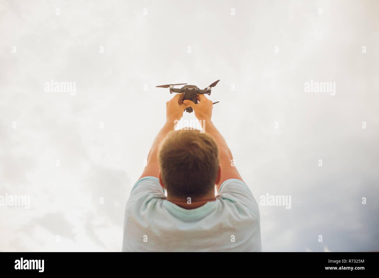 Giovane Azienda drone prima del volo in natura. Pretty guy preparare per il pilota quadrocopter outdoor sollevato Immagini Stock