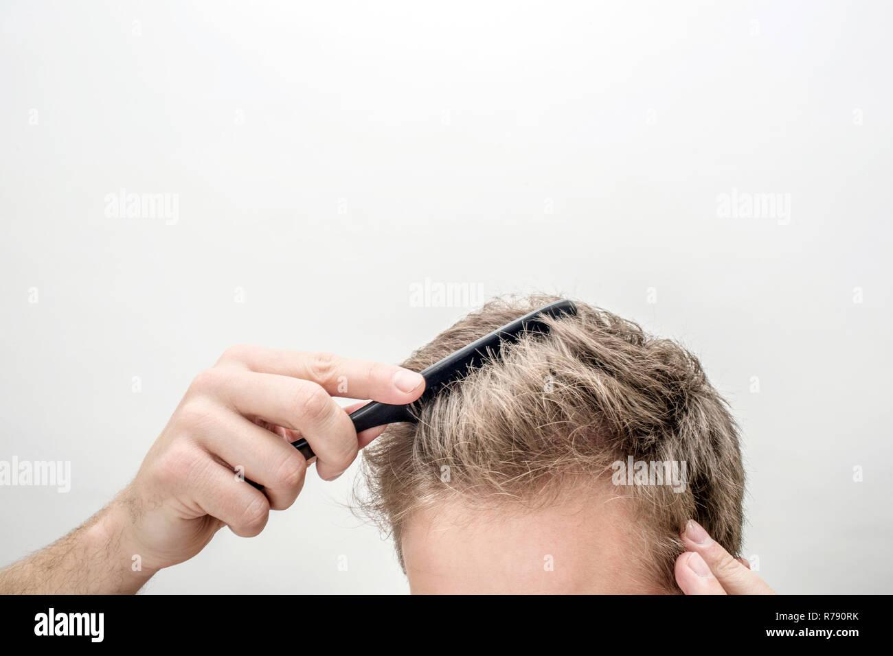 Vista di taglio del giovane biondo uomo spazzolare i capelli. Isolato su sfondo bianco. Immagini Stock