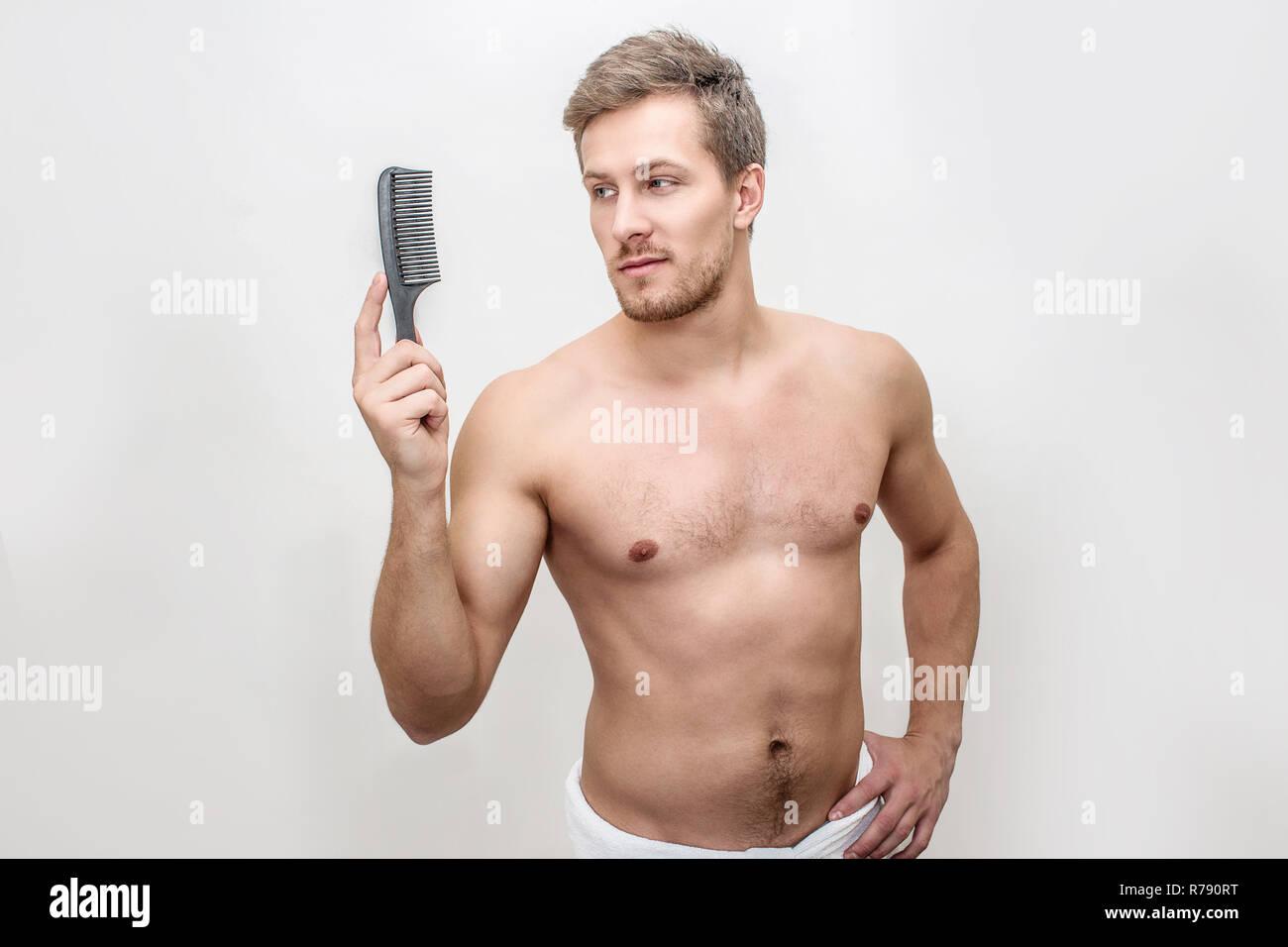 Bel giovane tenere la spazzola in mani. Egli guarda a. Il ragazzo è shirtless. Egli indossa asciugamano intorno ai fianchi. Isolato su sfondo bianco. Immagini Stock