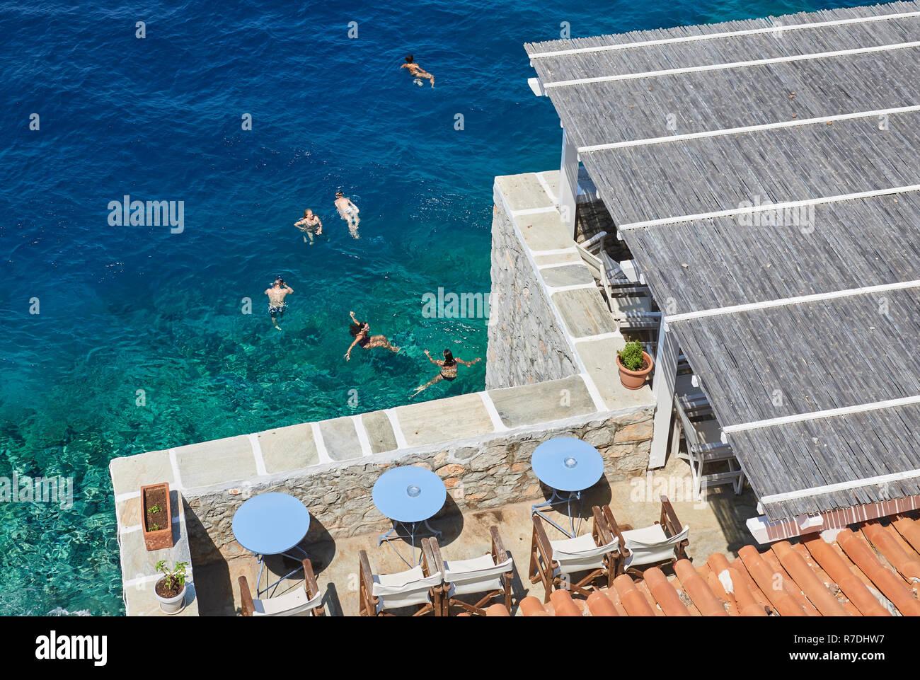 Persone per godersi il sole e il cristallo turquise mare a Hydra Island Immagini Stock