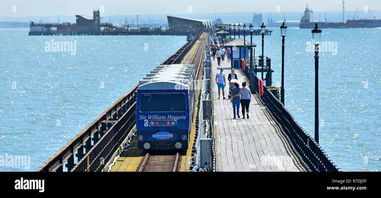Teleobiettivo seascape River Thames Estuary Southend Pier & giovane camminando lungo il molo i mezzi di trasporto pubblici Stazione treno passa sul modo di pier head Essex REGNO UNITO Immagini Stock