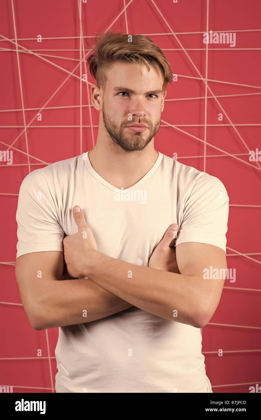 Uomo in bianco tshirt con mani piegate. Ragazzo con la barba barba lunga  faccia. 44933485caf8