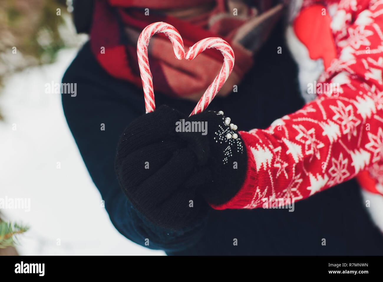 Lecca-lecca bastone in mano in mitten neve sullo sfondo i dolci di natale concetto. andies in forma di cuore. Candy in mano con un guanto su uno sfondo di neve. Foto Stock