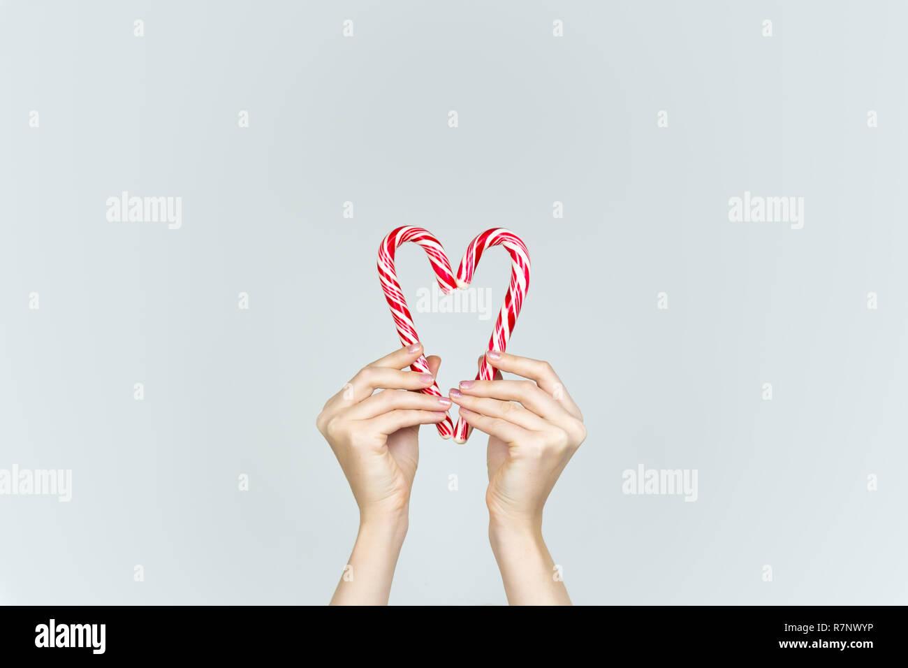 Amore e bontà del concetto: mani tenere due candy canes rendendo la forma del cuore. Cuore formata da due bianchi e rossi dolci di Natale. Immagini Stock