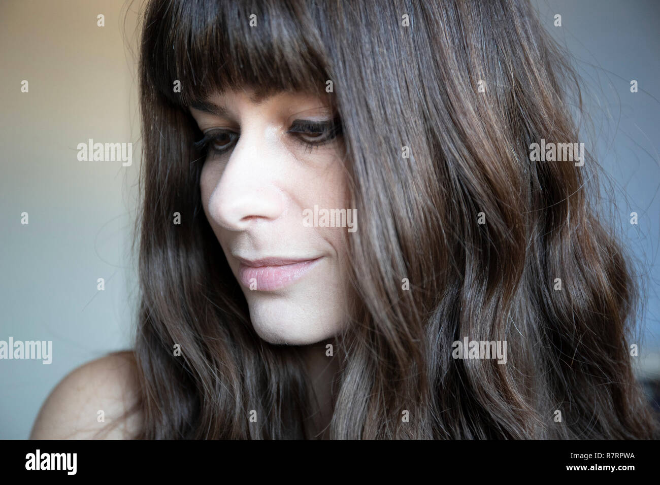 Giovane donna close-up tre quarti ritratto. Caucasian marrone con capelli lunghi e bangs. Espressione sorridente, guardando verso il basso. Immagini Stock
