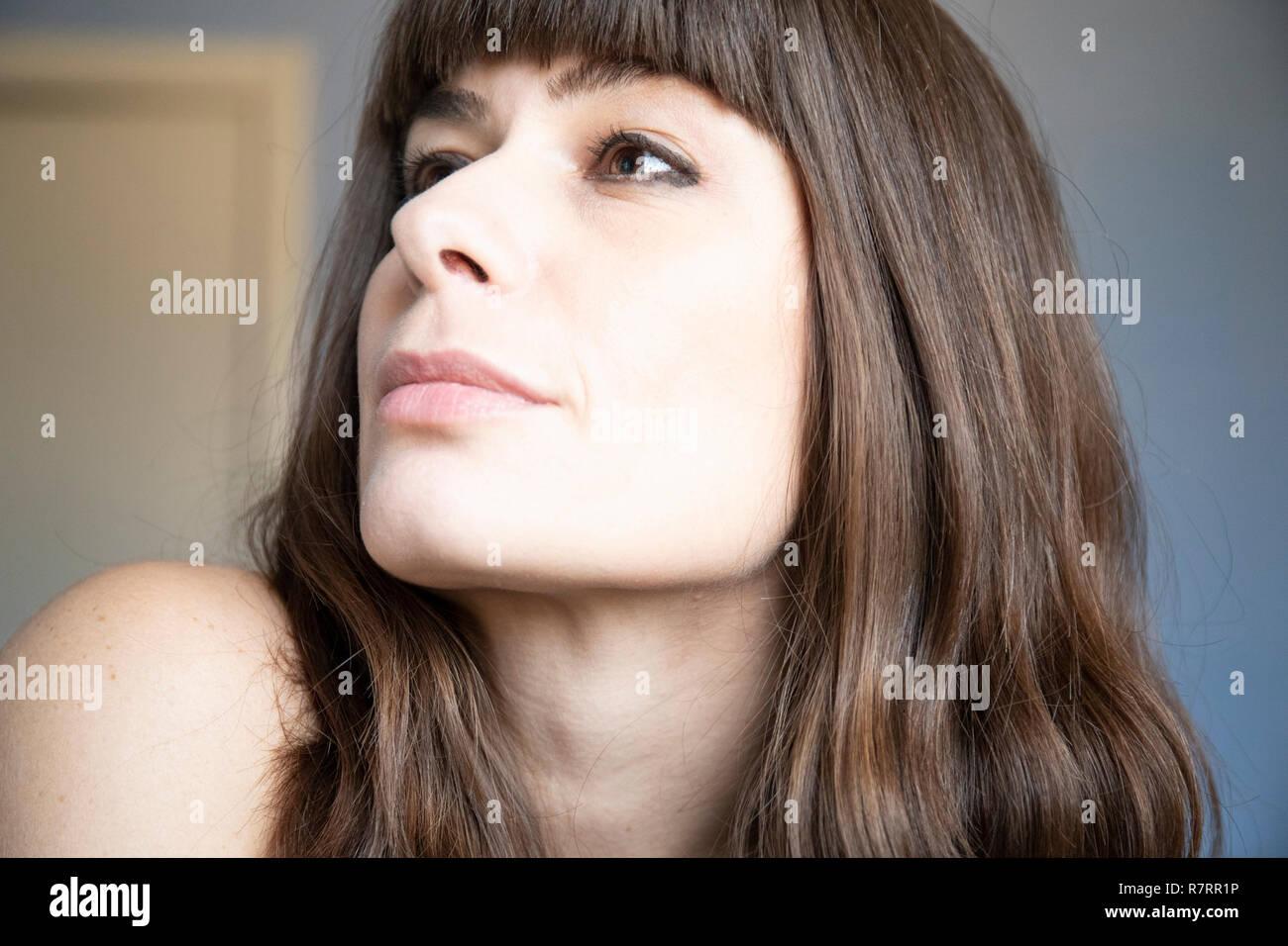 Giovane donna close-up tre quarti ritratto. Caucasian marrone con capelli lunghi e bangs. Espressione sorridente, guardando verso l'alto. Sollevate la mascella. Immagini Stock