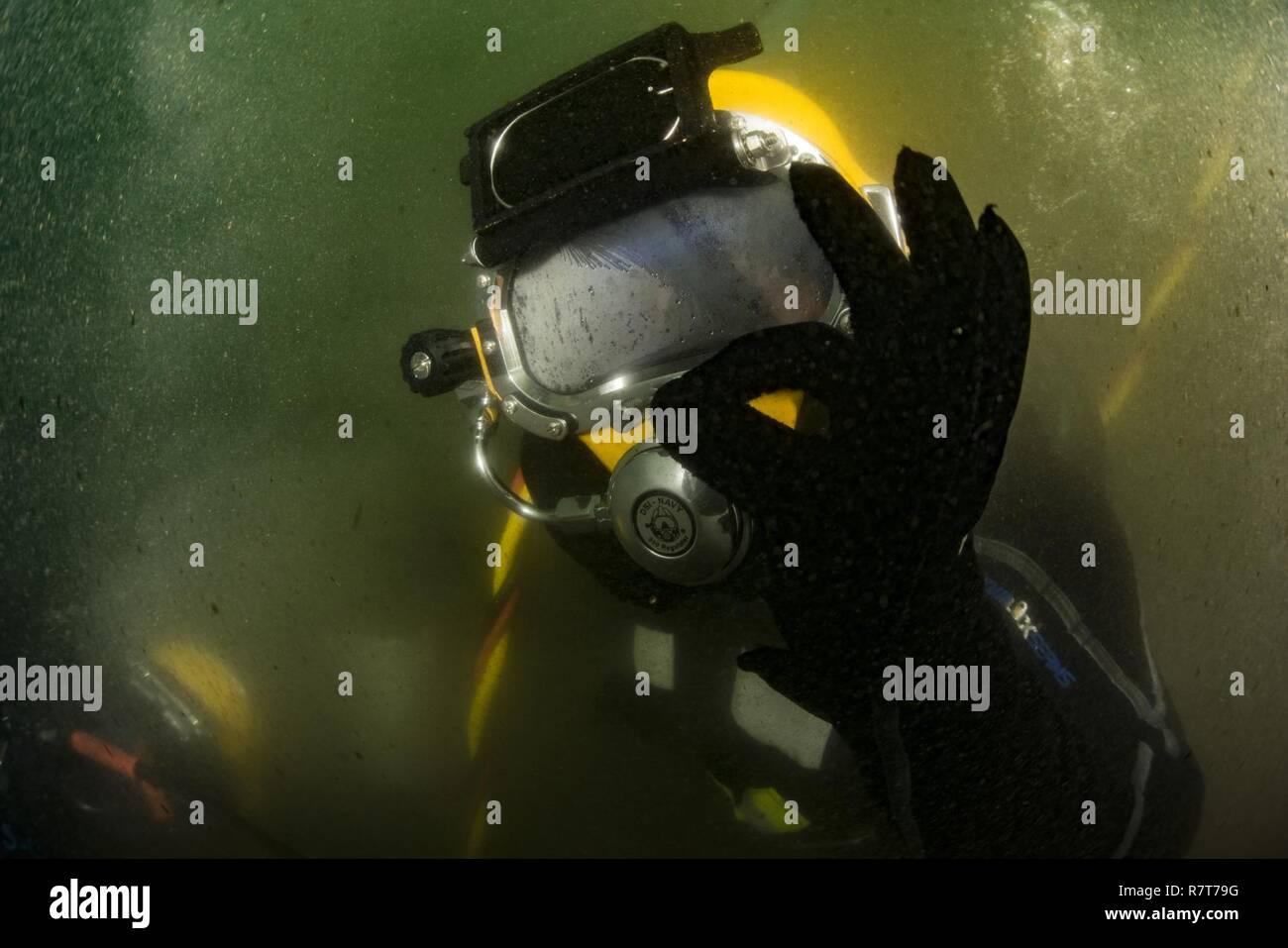 Operatore di apparecchiature di terza classe Thomas Dahlke, assegnato alla costruzione subacquea Team (UCT) 2, dà il segno OK prima di iniziare a bassa visibilità subacquea evoluzione di taglio con un subacqueo assegnati alla Repubblica di Corea (ROK) UCT in Jinhae, Rok, come parte di esercitare il puledro Eagle Aprile 6, 2017. Puledro Eagle è un annuale bilaterale esercizio di formazione progettate per migliorare la disponibilità degli Stati Uniti e le forze di Rok e la loro capacità di lavorare insieme durante una crisi. I marinai di costruzione Dive distacco Charlie sono sulla seconda tappa della loro distribuzione dove sono le ispezioni, maintena Immagini Stock