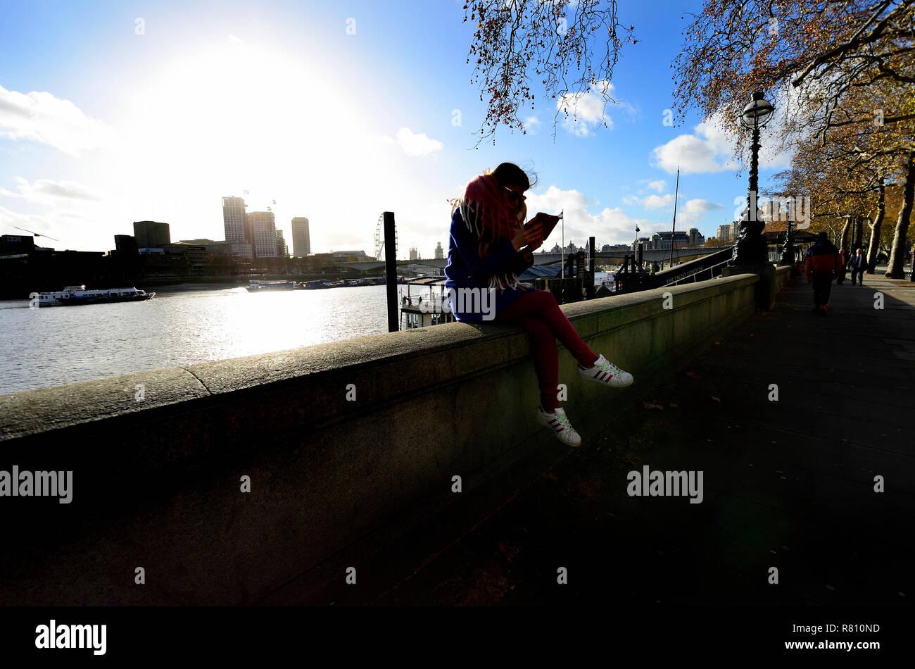 Giovane donna sul suo telefono cellulare, Victoria Embankment, Londra, Inghilterra, Regno Unito. Inverno Immagini Stock