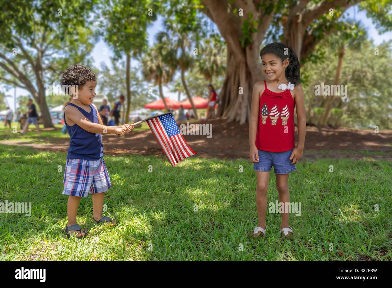 Ispanico fratello e sorella gioca alla comunità del parco sotto l'ombra di un grande albero come egli tiene la bandiera americana attaccato ad un bastone. Immagini Stock