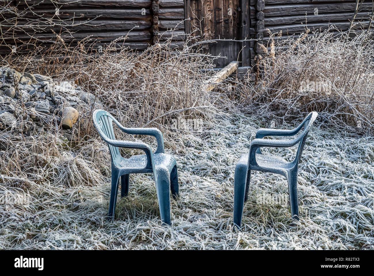 Blu di due sedie di plastica con rime congelati in un giardino rurale con rustici agriturismo ed erba ricoperto di ghiaccio freddo trasformata per forte gradiente frost un inizio inverno mattina Foto Stock