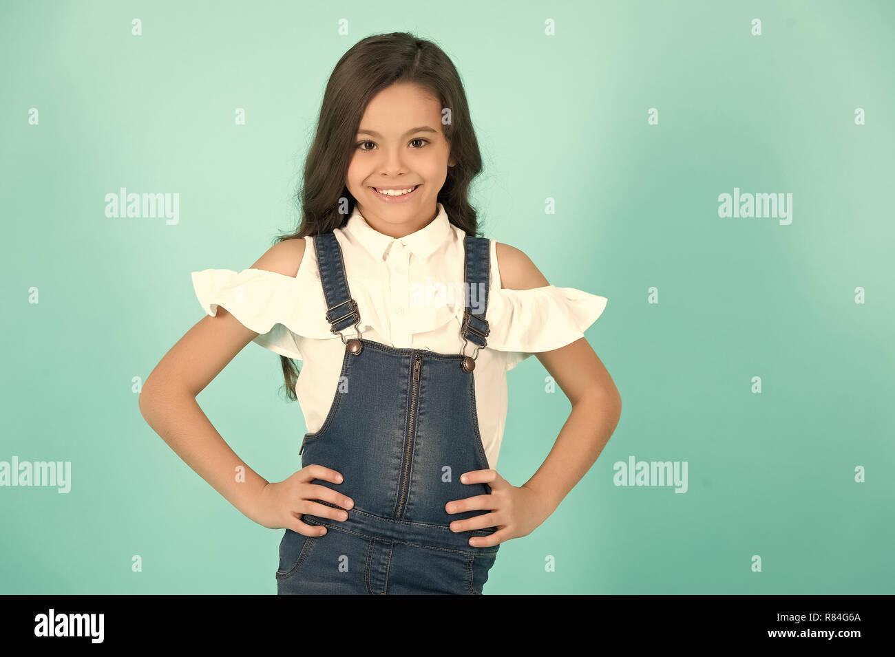 Kid Sorriso ragazza nel quartiere alla moda di jeans generale con le mani sul hip su sfondo blu. Moda, bellezza, stile look. Bambino felice, concetto di infanzia. Immagini Stock