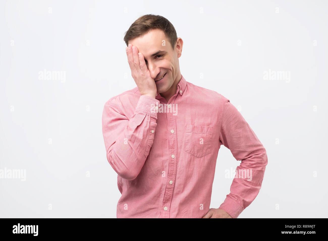 Uomo in camicia rosa guardando la fotocamera con astuzia espressione divertente, chiude la sua bocca. Immagini Stock