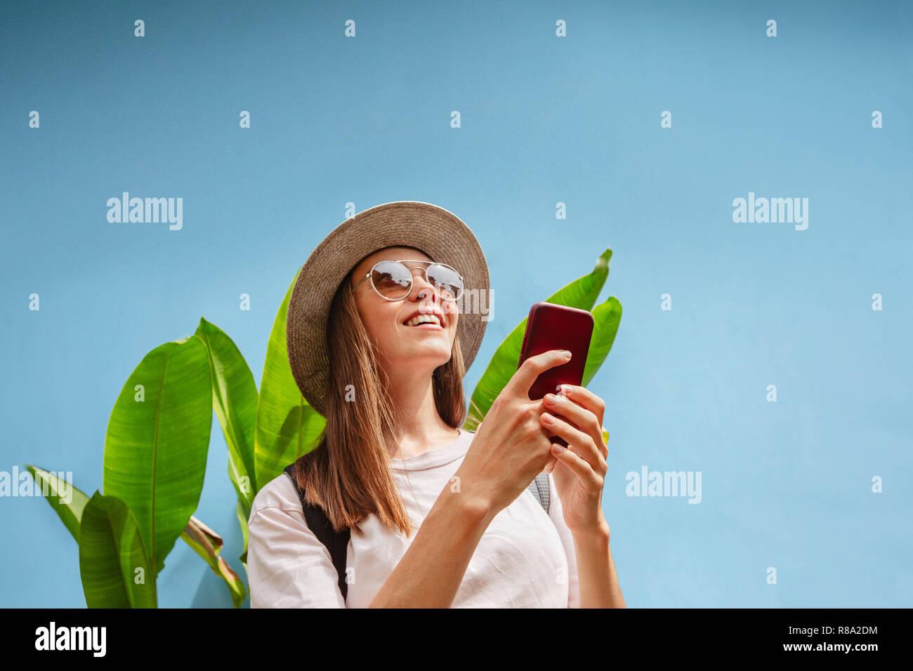 Eccitato giovane femmina in vacanza utilizza smartphone Immagini Stock
