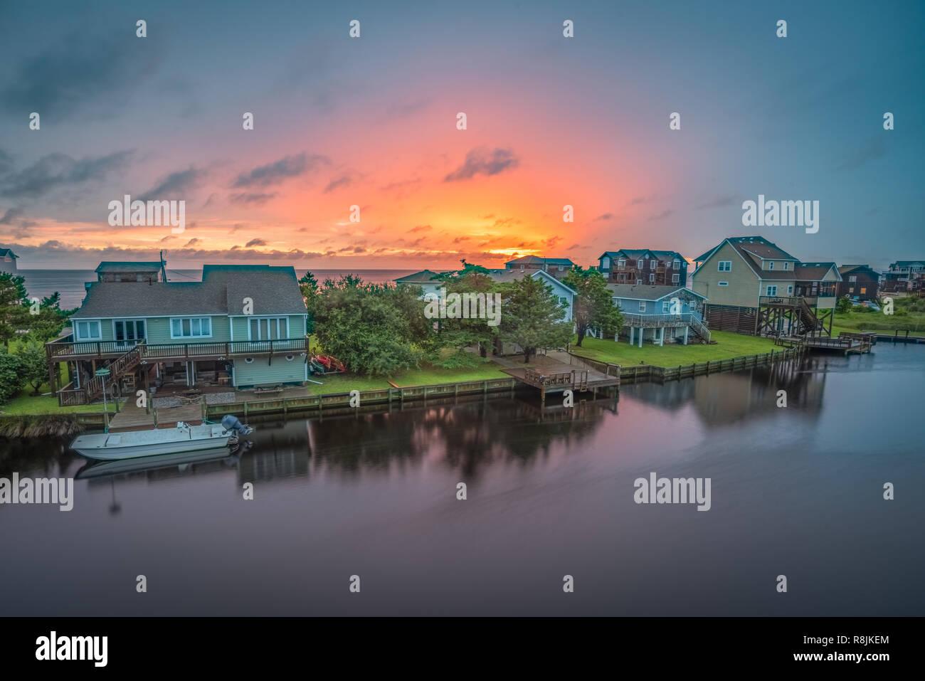 Il sole tramonta dietro una fila di waterfront cottage sui Hatteras Island, NC. Foto Stock