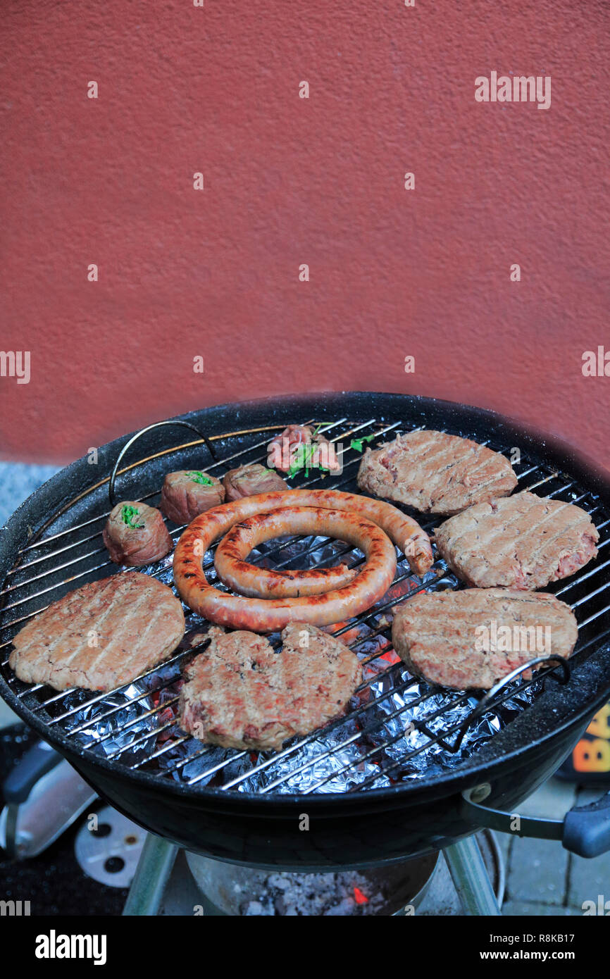 Risoni, Burger, Wurst und Fleischröllchen auf dem Holzkohle Grill Immagini Stock