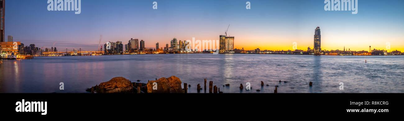 Vista panoramica della East River di notte con il centro cittadino di Long Island in background Immagini Stock