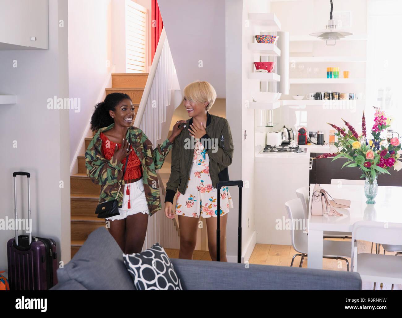 Entusiasti di donne giovani amici arrivando a Affitto casa Immagini Stock