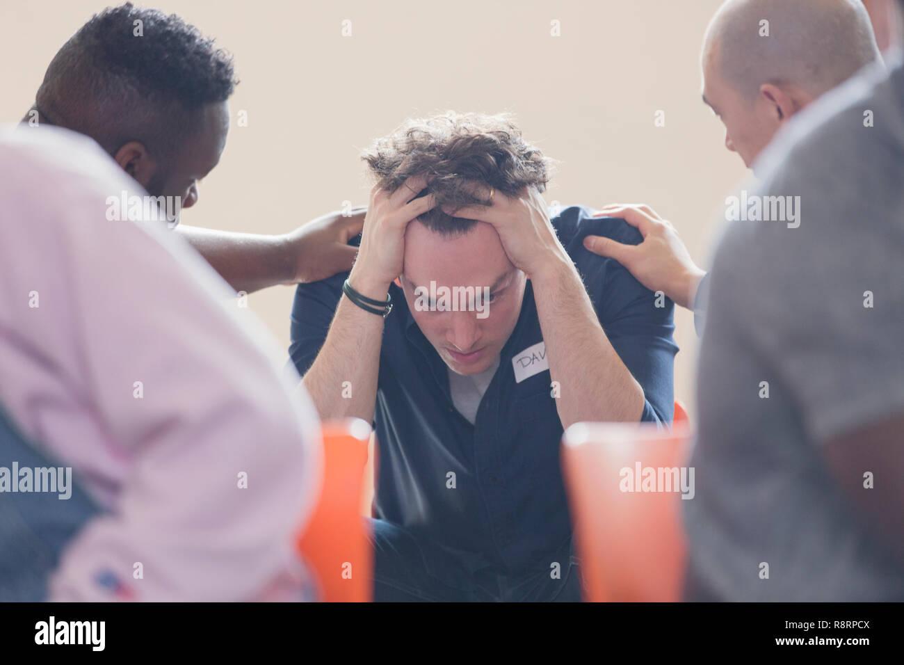 Gli uomini consolante sconvolto l uomo nella terapia di gruppo Immagini Stock