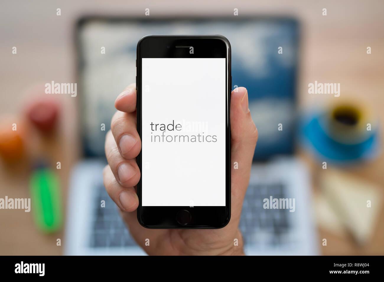 Un uomo guarda al suo iPhone che visualizza il commercio logo informatica (solo uso editoriale). Immagini Stock