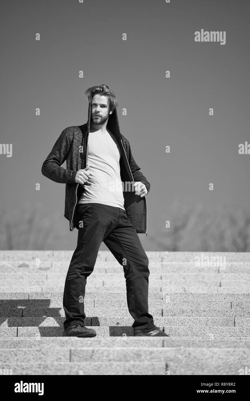 Concetto di fasi. Giovane uomo in felpa con cappuccio stand sui passi di sunny blue sky. Passi per il successo 1. La chiave è la libertà nelle fasi. Immagini Stock