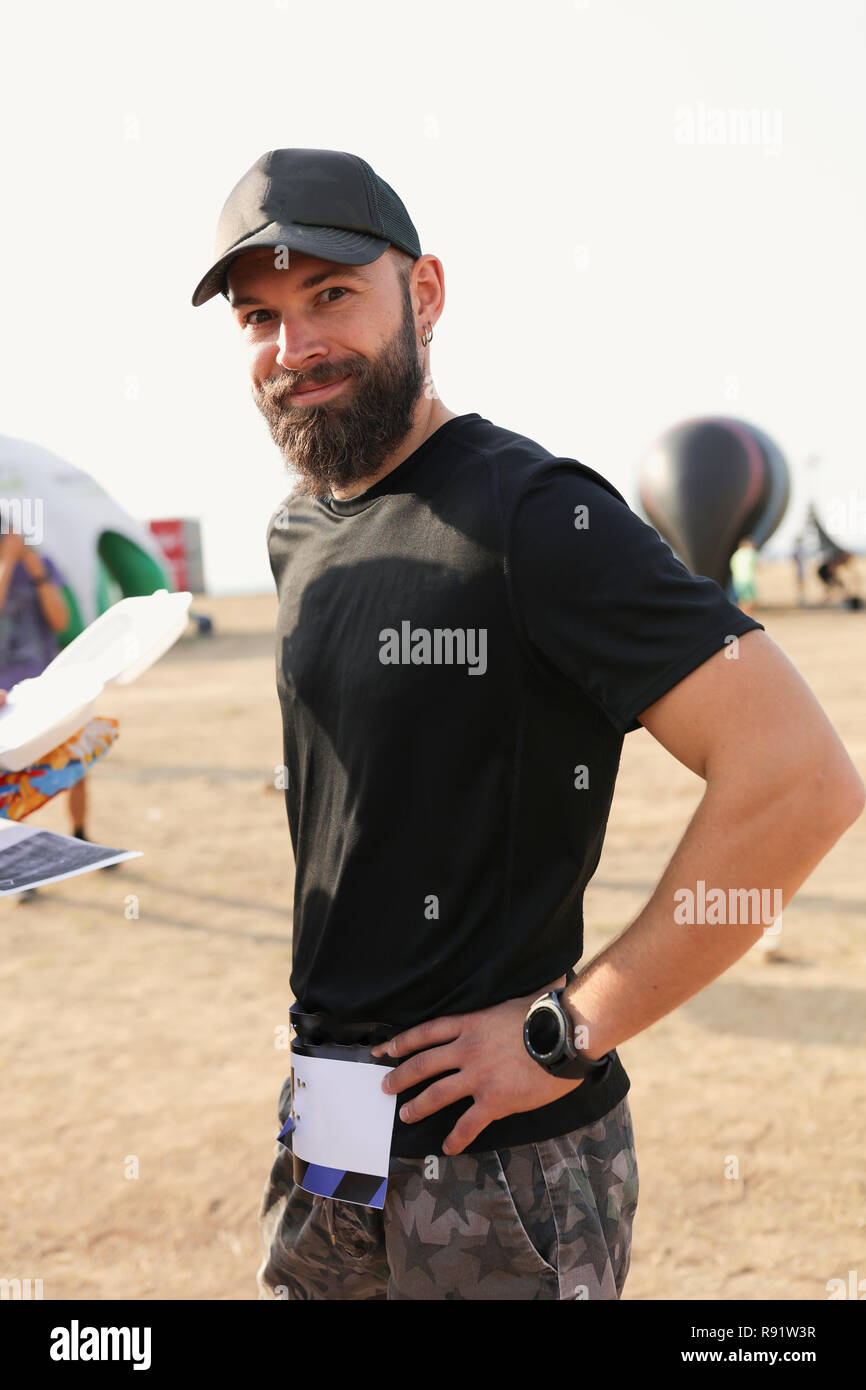 Ritratto di un ragazzo di sport con la barba in black t-shirt e pantaloncini 927b633c99e7
