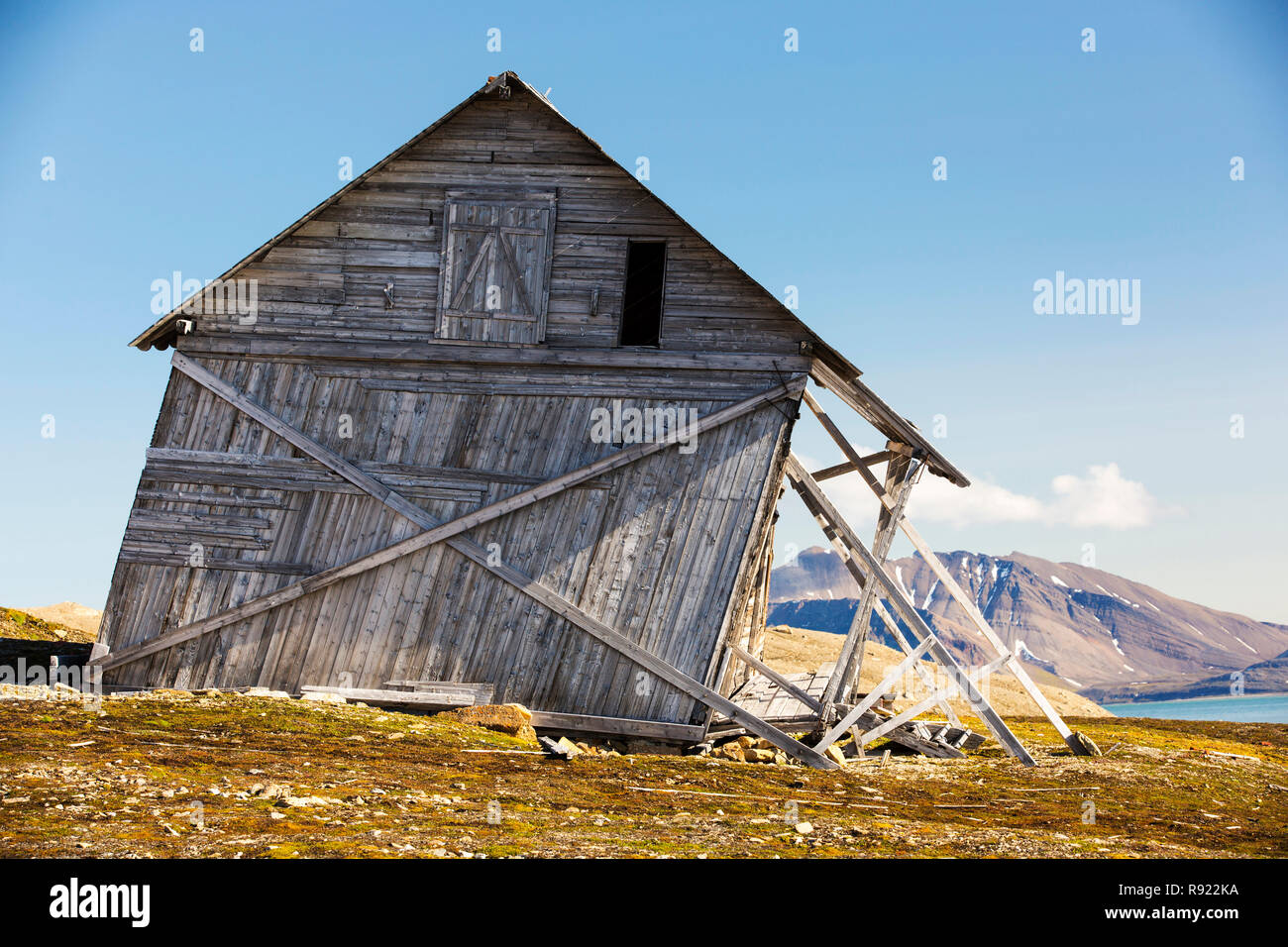 Una vecchia casa a Recherchefjorden (77Ã'áẁž31Ãḃ™n 14Ã'áẁž36Ãḃ™e), Van Keulenfjorden, Spitsbergen, Svalbard. Essa viene progressivamente scivolare verso il basso a causa della pendenza di solifluction e permafrost fuso. Il cambiamento climatico sta accelerando il permafrost fondere e causando ingenti danni in tutta la regione artica. È anche uno degli anelli di retroazione che exascerbate il cambiamento climatico, come il permafrost si blocca a miliardi di tonnellate di metano (un gas ad effetto serra 23 volte più potente del C02), come il permafrost si scioglie il metano viene rilasciato in atmosfera con porentially conseguenze disastrose. Immagini Stock