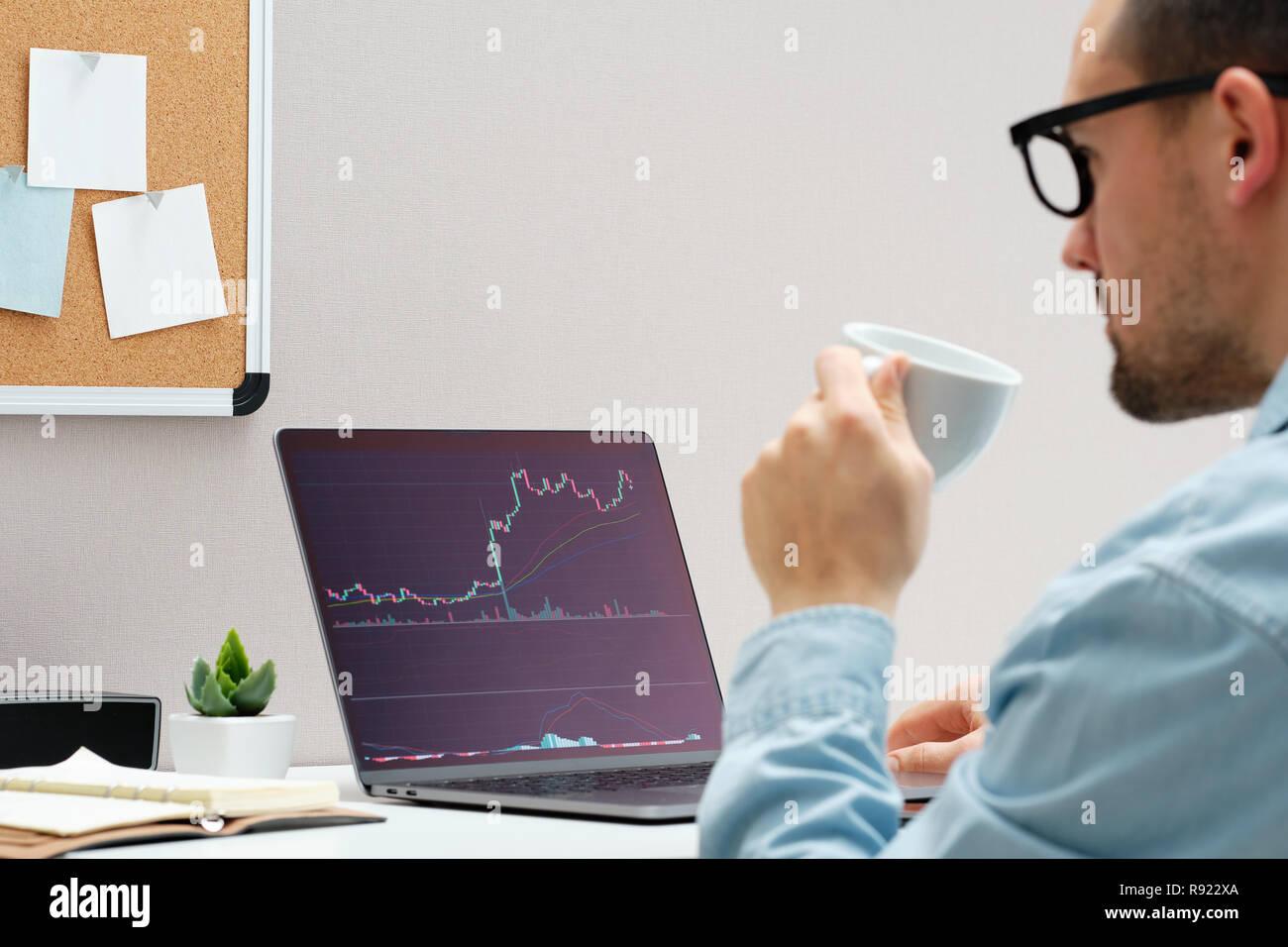 Investor guardando il cambiamento del mercato azionario su notebook Immagini Stock