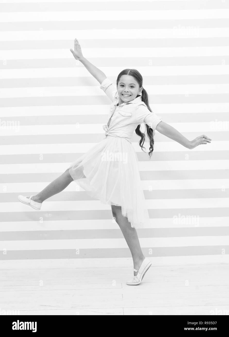 Concetto di bambino. Felice piccolo bambino dancing. Bambino Sorriso ragazza in abito di moda. Bambino e infanzia. senso di libertà. Immagini Stock