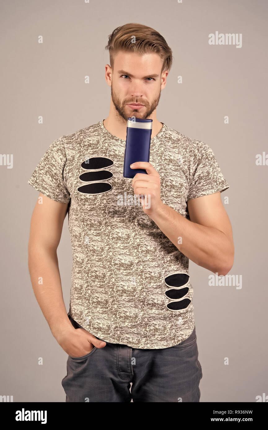 Uomo con gel o bottiglia di shampoo in mano. Igiene 459a0001c33a