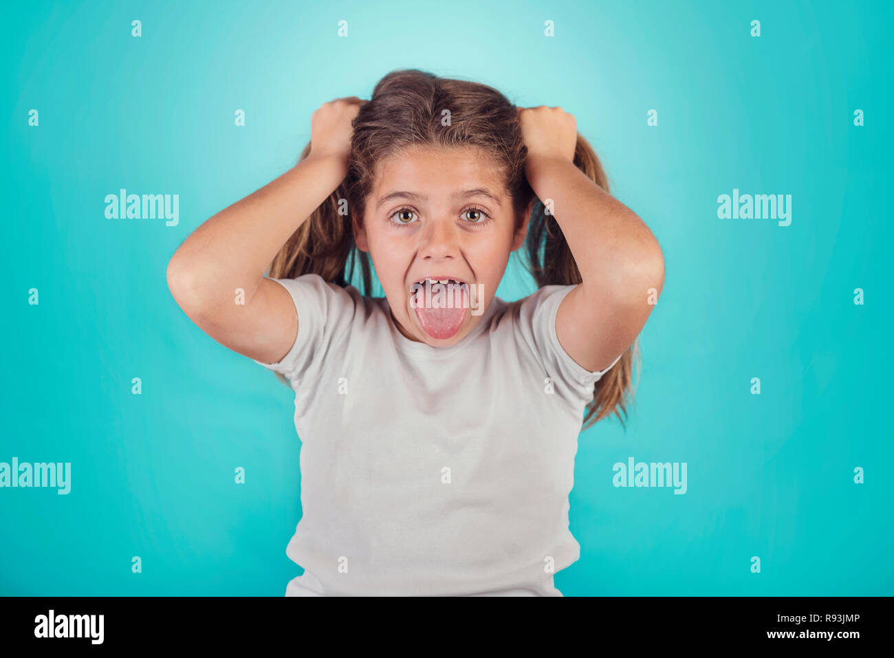 Ritratto di angry girl su sfondo blu Foto Stock